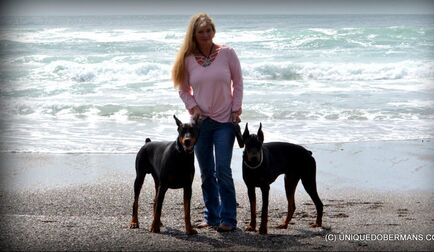 Picture of pretty lady with two male Dobermans on the Oregon coast beach